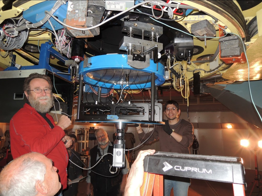 The guiding camera is seen at the bottom of the du Pont Telescope at Las Campanas Observatory in Chile. Fred Hearty (head, bottom left), Paul Harding (left, red jacket), John Wilson (behind Paul), French Leger (behind the guiding camera), Juan Trujillo (to right of guiding camera), and John Parejko (who took the picture) are responsible for the recent progress.